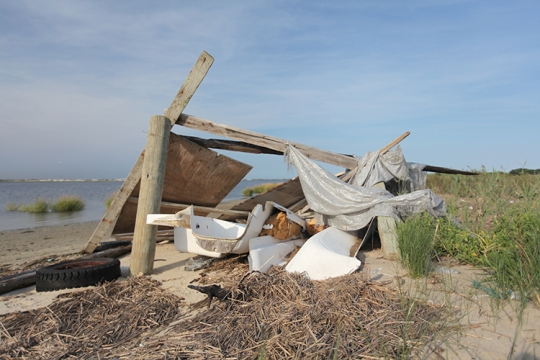 A beach shelter built from salvaged garbage and tarps.