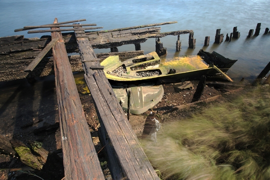 Yellowing remains of a small vessel permanently docked in Dubos Point.