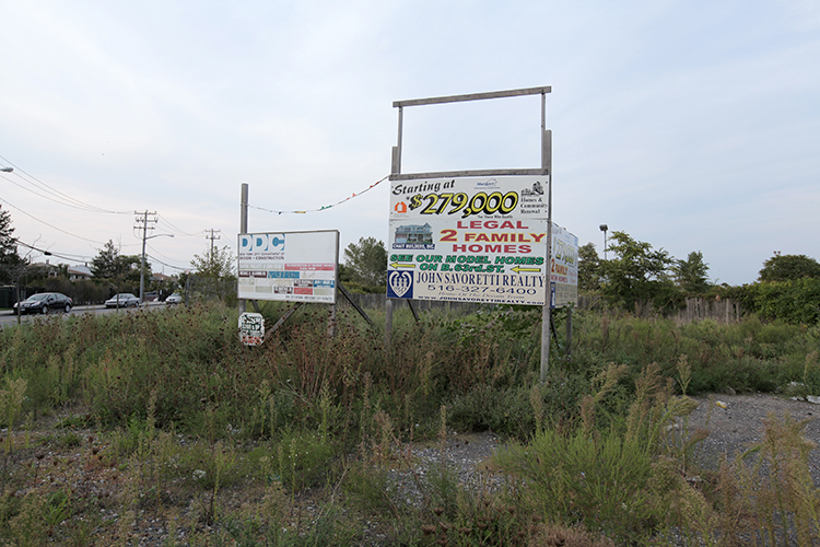 An overgrown lot advertising yet another housing development.