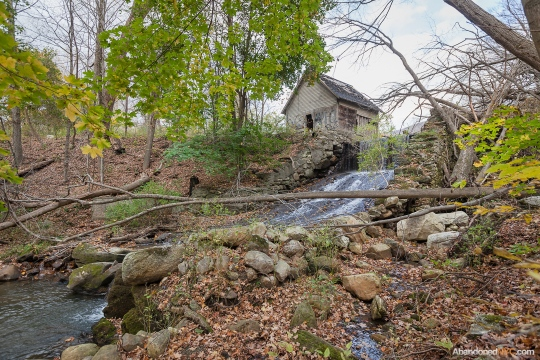 An abandoned pumphouse sits beside a waterfall in the woods near the railroad tracks.