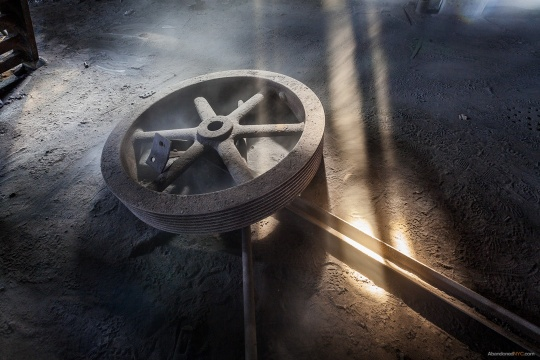 As the light lengthens toward day's end, blowing soot is illuminated by a shaft of light near a giant wheel.