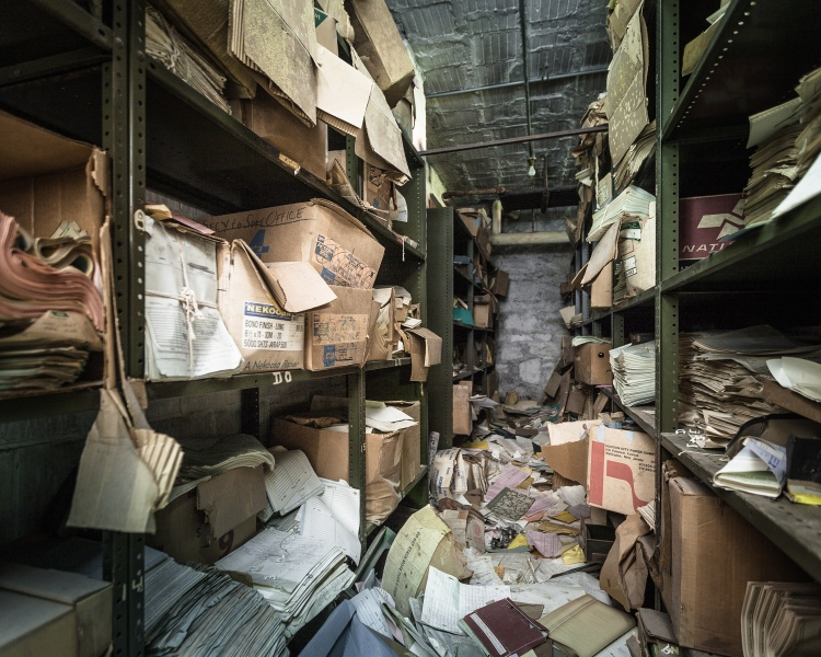 The file room contained 6 or 7 aisles of shelving piled high with records.
