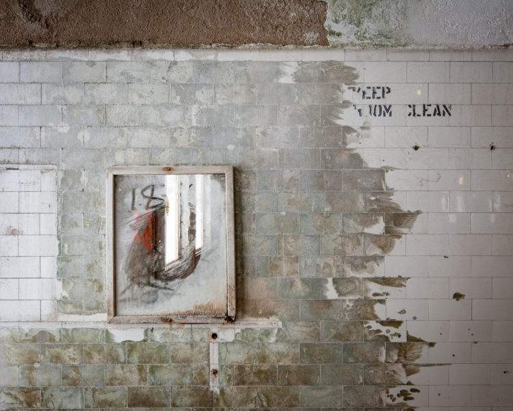 A bathroom mirror and friendly reminder were left behind in the gutted interior.