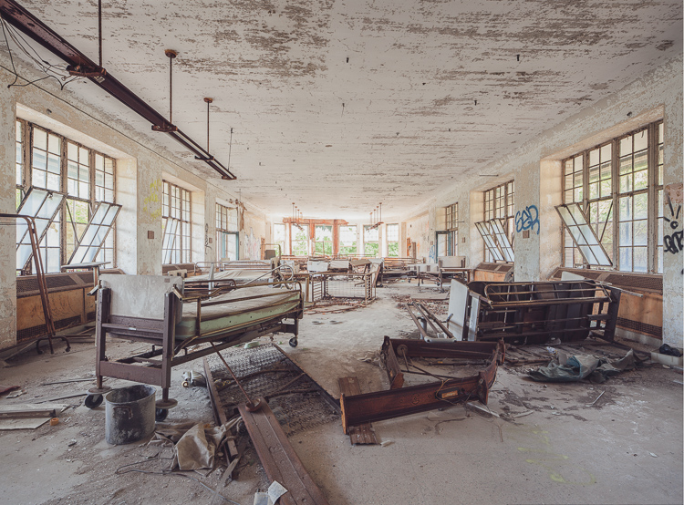 Hospital beds, cribs, and equipment left behind in a day room on a lower floor.